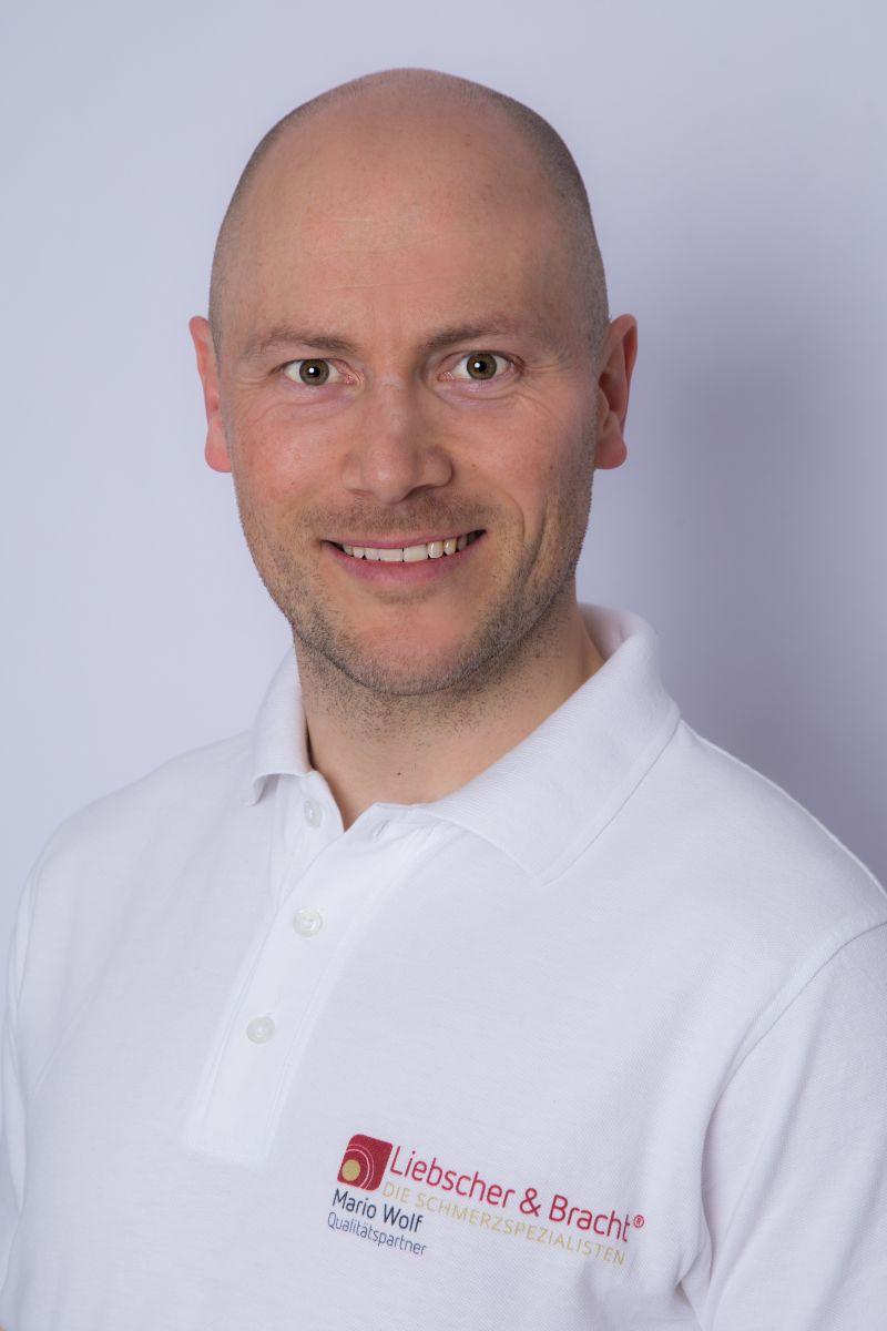 Das Foto zeigt Mario Wolf aus Dresden. Der Physiotherapeut trägt ein weißes Liebscher & Bracht T-Shirt und hat eine Glatze sowie einen Dreitagebart.