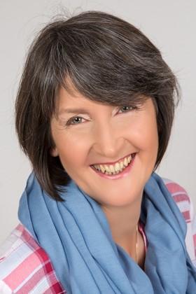 Das Foto zeigt Marion Hochberg aus 06846 Dessau-Roßlau lachend vor einem hellen Hintergrund. Sie hat kinnlange schwarz graue Haare und trägt einen hellblauen Schal sowie eine rosa rote Bluse.