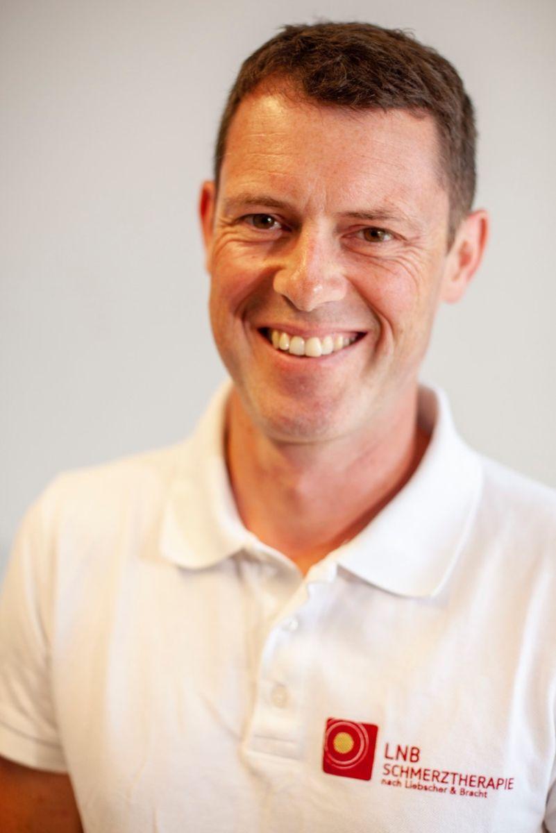 Auf dem Foto sieht man den Physiotherapeuten Markus Kraft aus Schwäbisch Hall. Er lacht in die Kamera und hat kurze braune Haare. Auf dem Foto trägt er ein weißes Liebscher & Bracht Polo T-Shirt.