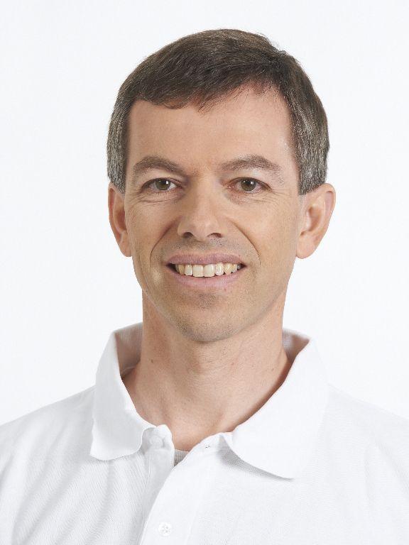Das Portraitfoto von Markus Müller ist vor weißem Hintergrund aufgenommen. Er hat braunes Haar und trägt ein weißes Polo T-Shirt.