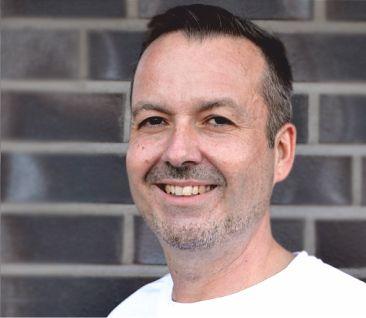 Auf dem Foto steht Markus Zach-Landvogt, der in Bad Zwischenahn praktiziert. Er steht vor einer dunklen Backsteinwand. Er hat dunkle Haare und einen Dreitagebart.