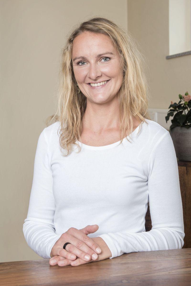 Das Foto zeigt die Physiotherapeutin Marleen Koch aus Freiburg sitzend an einem Tisch. Sie lacht in die Kamera und hat lange blonde Haare. Sie trägt ein weißes langärmliges T-Shirt und hat die Hände auf den Tisch gelegt.