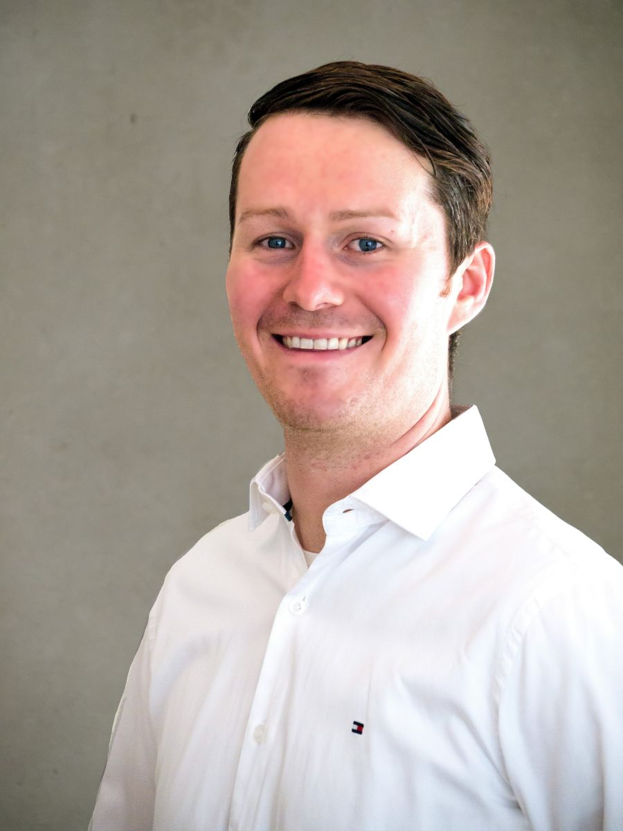Martin Weißensteiner aus Graz, steht schräg und lächelt in die Kamera. Der Hintergrund ist hellgrau und er trägt ein weißes Hemd. Er hat blaue Augen und kurze braune Haare, die zur Seite gegelt sind.