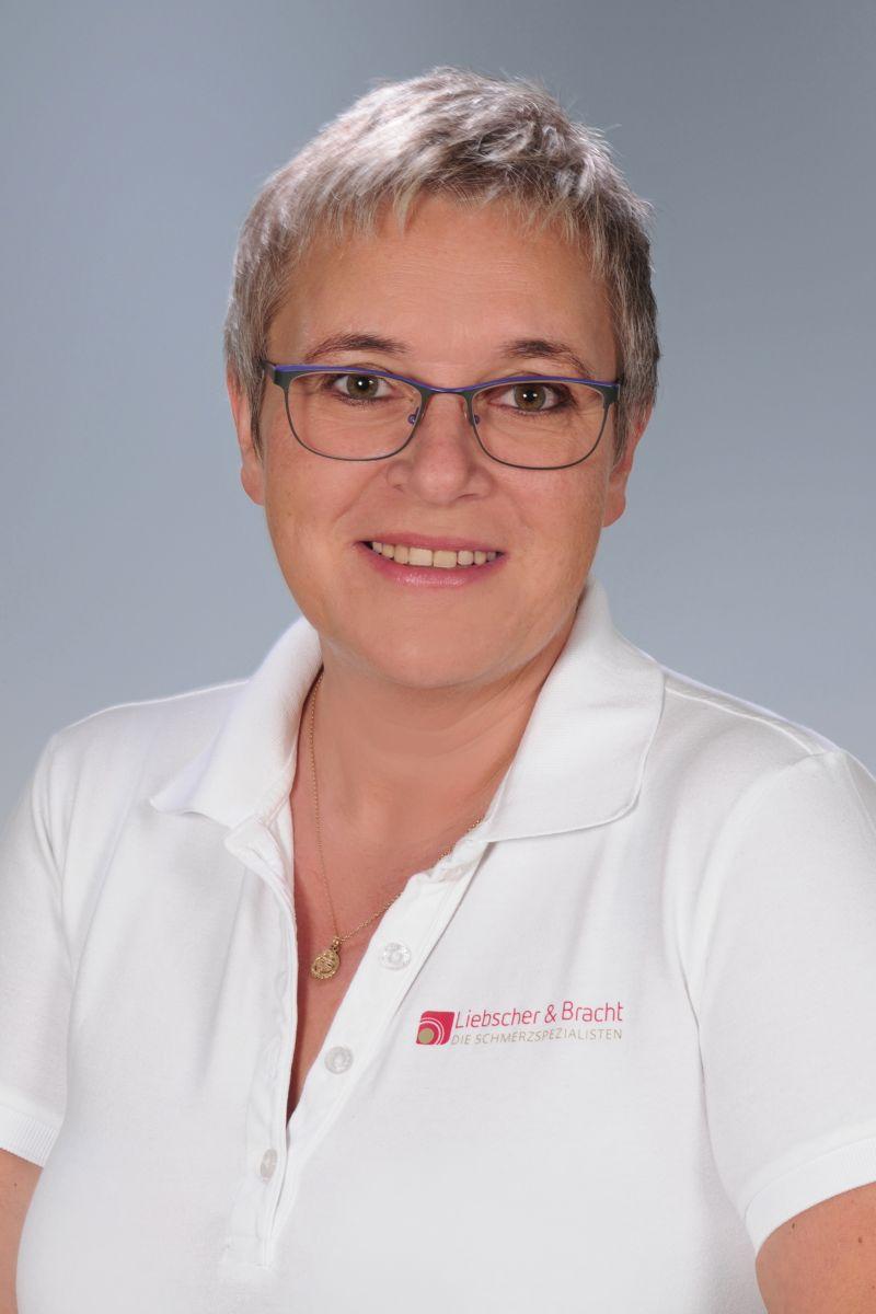 Das Foto zeigt die FAYO Trainerin Martina Schröckelsberger vor einem hellgrauen Hintergrund. Sie hat kurze blonde Haare und trägt eine blaue eckige Brille. Dazu trägt Sie ein weißes Liebscher & Bracht Polo T-Shirt und lächelt in die Kamera.
