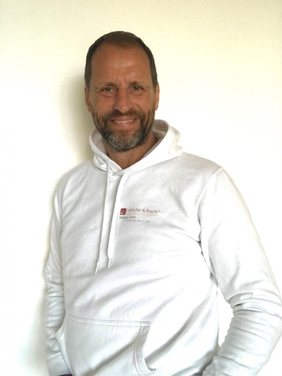 Das Foto zeigt Mathias Grom vor einem hellen Hintergrund wie er in die Kamera lächelt. Er hat kurze braune Haare und einen braun grauen Dreitagebart. Auf dem Bild trägt er einen weißen Liebscher & Bracht Pullover.