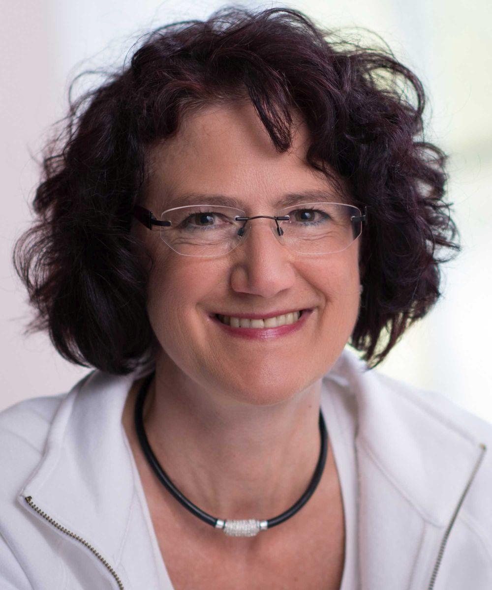 Die Heilpraktikerin Meike Lutz aus Pleidelsheim sitzt vor einem hellen lichtgefluteten Hintergrund. Sie hat dunkle mittellange lockige Haare und trägt neben einer weißen Jacke und T-Shirt eine schwarze Kette und eine randlose Brille.