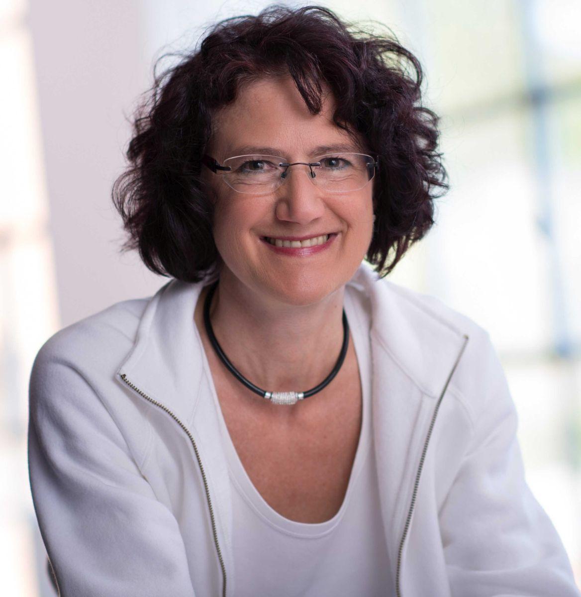 Die Heilpraktikerin Meike Lutz aus Heilbronn sitzt fröhlich vor einem hellen lichtgefluteten Hintergrund. Sie hat dunkle mittellange lockige Haare und trägt neben einer weißen Jacke und T-Shirt eine schwarze Kette und eine randlose Brille.