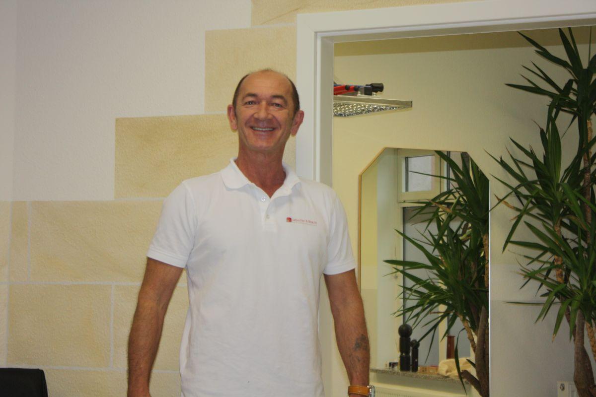 Michael Appelius, Heilpraktiker aus Kronach, steht vor einem hellgelben Praxisraum. Er trägt ein weißes Liebscher & Bracht Polo T-Shirt und hat eine Halbglatze.