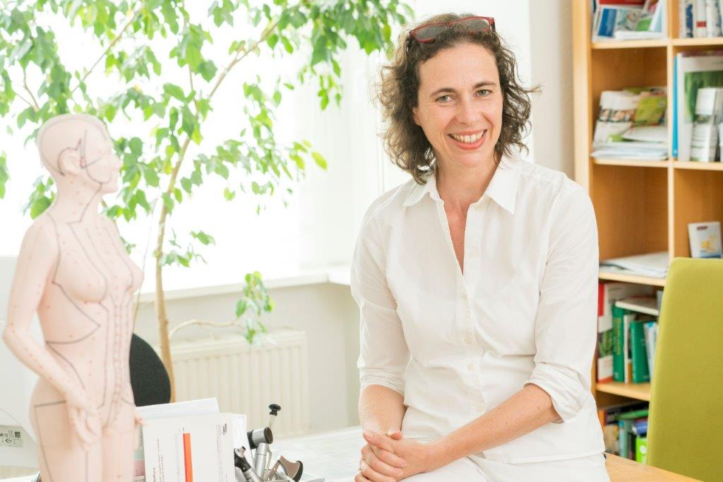 Das Foto zeigt Michèle Klara Lux aus Berlin in der Umgebung ihres Praxiszimmers. Neben ihr steht ein anatomisches Modell. Sie hat schulterlange braune Haare, die sich locken und trägt eine weiße Bluse sowie eine weiße Hose.
