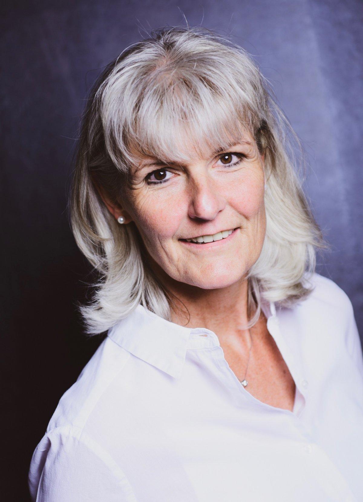 Die Physiotherapeutin Annette Dilger sitzt schräg vor einem dunklen Hintergrund. Sie lächelt und schaut dabei ein wenig nach oben in die Kamera. Ihre grauen Haare trägt sie mittellang und mit einem geraden Pony. Auf dem Foto trägt sie eine weiße Bluse.