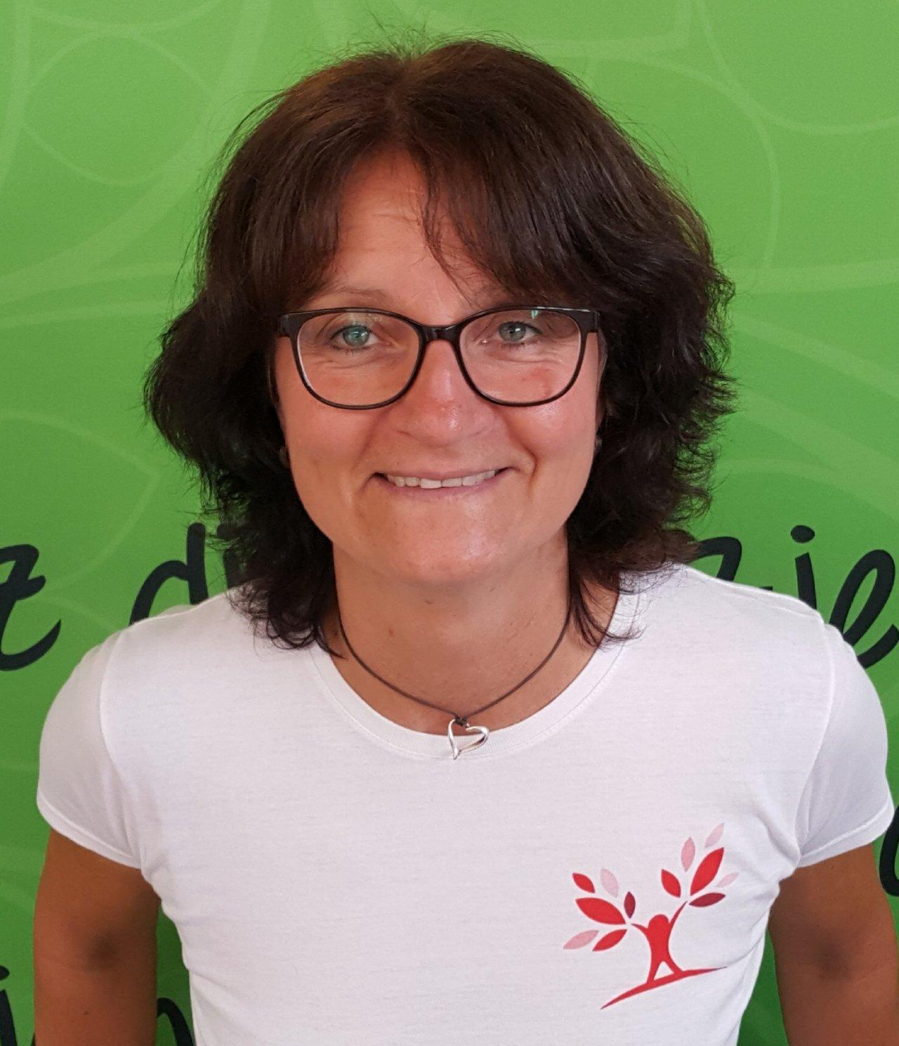 Auf dem Foto ist Monika Stottan aus Wien vor einem grünen Hintergrund zu sehen. Sie hat kinnlange braune gestufte Haare und einen Pony. Auf dem Bild trägt sie eine eckige schwarze Brille, eine schwarze Kette und ein weißes T-Shirt mit einem roten Aufdruck