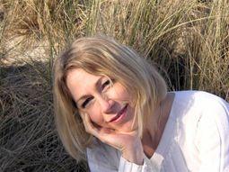 Myriam Ott-Jacquet sieht man vor dem Hintergrund einer Düne mit Dünengras sitzen. Sie hat schulterlange blonde Haare und lehnt ihren Kopf auf eine Hand. Sie lächelt in die Kamera und trägt eine weiße Bluse.