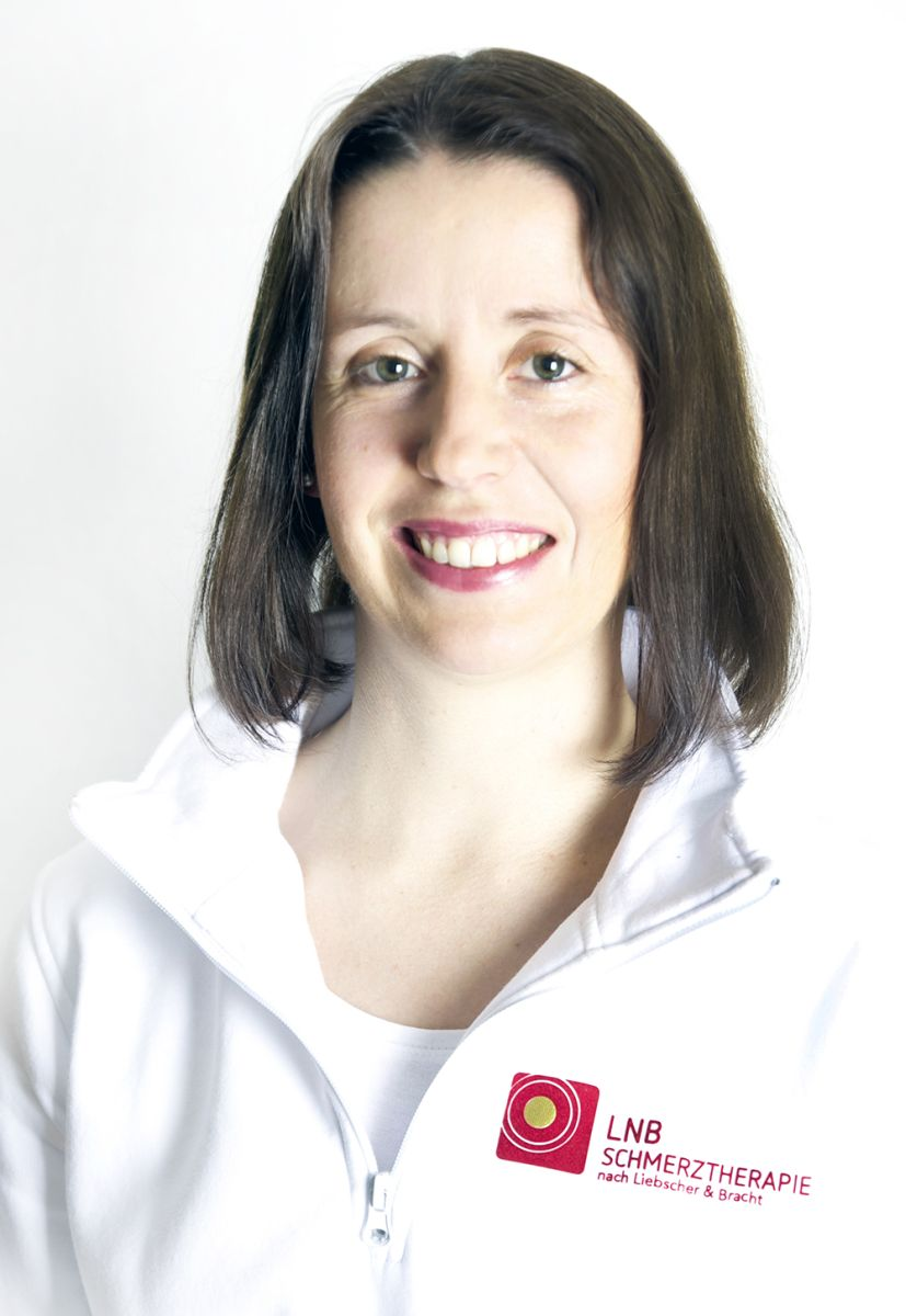Das Foto zeigt Nadine Fiebig aus Lage vor einem weißen Hintergrund. Sie hat mittellange braune Haare und trägt eine weiße Liebscher & Bracht Strickjacke.