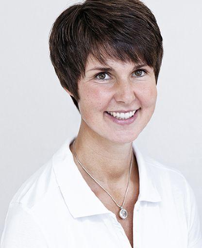 Die Heilpraktikerin Christina Springer sitzt schräg vor der Kamera und einem hellen Hintergrund. Sie hat kurze braune Haare und lacht in die Kamera. Sie trägt ein weißes Polo T-Shirt und eine silberne Kette.