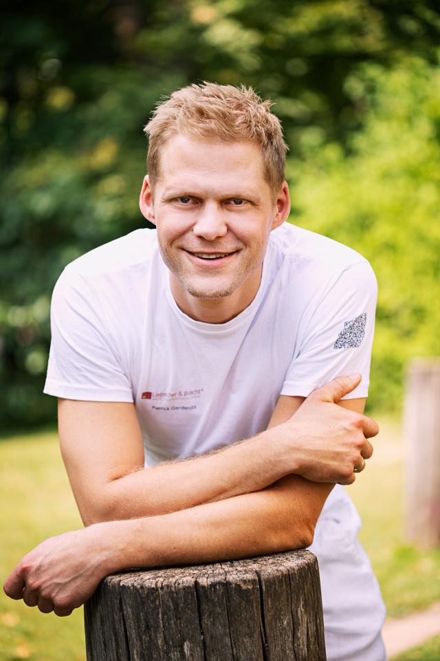 Patrick Gerdenits steht mit einem weißen Fayo T-Shirt vor grünem Hintergrund draußen. Er hat blonde Haare.
