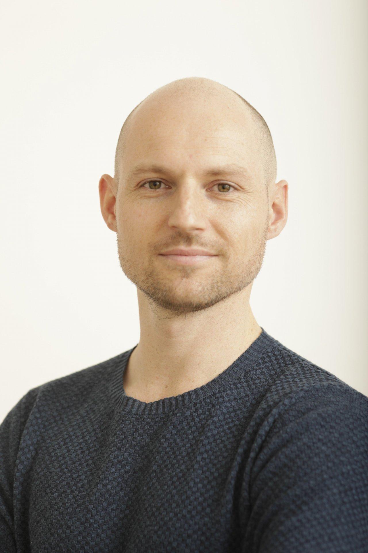 Der Diplom-Physiotherapeut aus Zürich Paul Hörter steht vor einem weißen Hintergrund. Man sieht ihn vom Oberkörper aufwärts. Er hat kurze blonde Haare und trägt ein Liebscher & Bracht Polo T-Shirt.