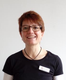 Peggy Herrmann ist vor einem weißen Hintergrund fotografiert. Sie hat kurze braun rote Haare und trägt eine eckige dunkle Brille, sowie ein schwarzes T-Shirt.