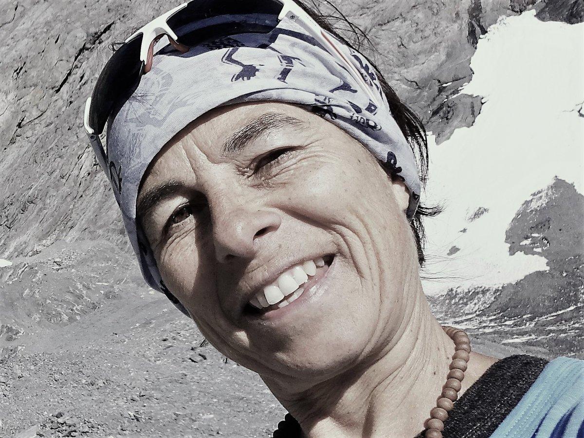 Auf dem Foto ist Petra Bittel aus Sursee zu sehen. Im Hintergrund erkennt man eine karge Landschaft und einen Schneezunge. Sie trägt ein Haarband und eine Sonnenbrille auf dem Kopf. Sie lächelt in die Kamera.