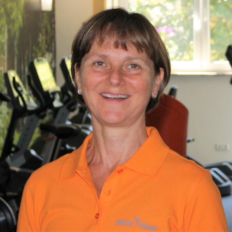 Auf dem Foto ist Petra Heynig aus 04838 Eilenburg zu sehen. Sie hat kurze braune Haare und einen geraden Pony. Im Hintergrund sieht man verschiedene Trainingsgeräte. Sie trägt ein orangenes Polo T-Shirt.