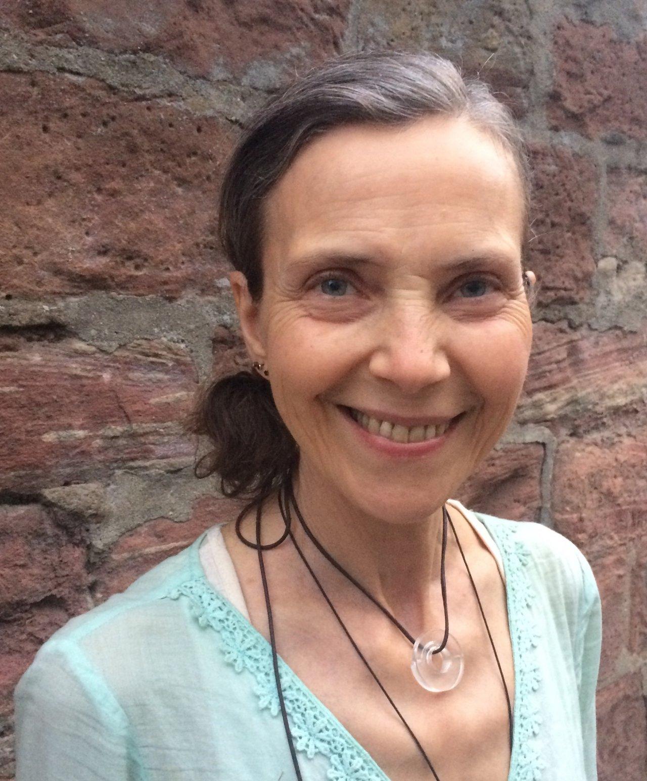 Auf dem Foto steht Petra lächelnd vor einer dunklen Steinwand. Sie hat ihren schwarz-grauen Haare als Zopf gebunden und lächelt in die Kamera. Auf dem Bild trägt sie eine schwarze Kette und ein türkisfarbenes T-Shirt.