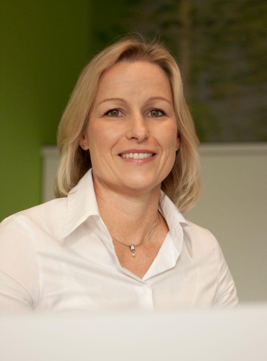 Petra Meyer, Physiotherapeutin aus 49191 Belm, sitzt vor einem grün weißen Hintergrund. Sie hat blonde mittellange Haare und trägt auf dem Foto eine weiße Bluse und eine silberne Kette.