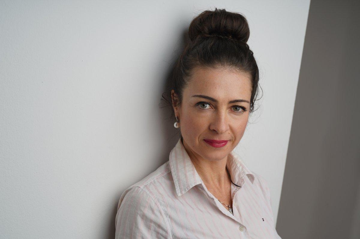 Das Foto zeigt Polina Schrott vor einer weißen Wand. Sie hat lange braune Haare, die sie als Dutt oben auf dem Kopf zusammen gebunden hat. Sie trägt Perlenohrringe und eine helle Bluse.