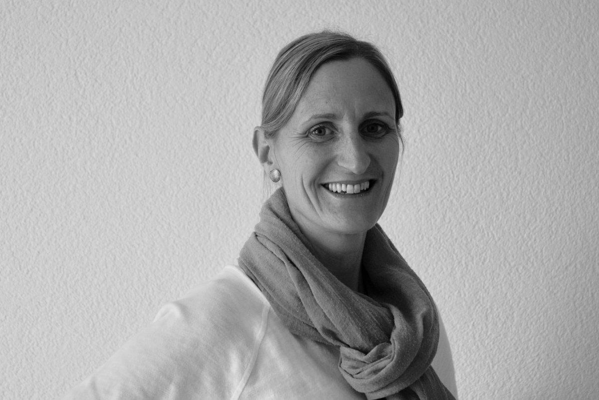 Das Schwarz-weiße Foto zeigt die Masseurin Priska Matti Wüthrich. Sie steht schräg zur Kamera und lächelt. Ihre Haare trägt sie zum Zopf und um den Hals trägt sie einen Schal.