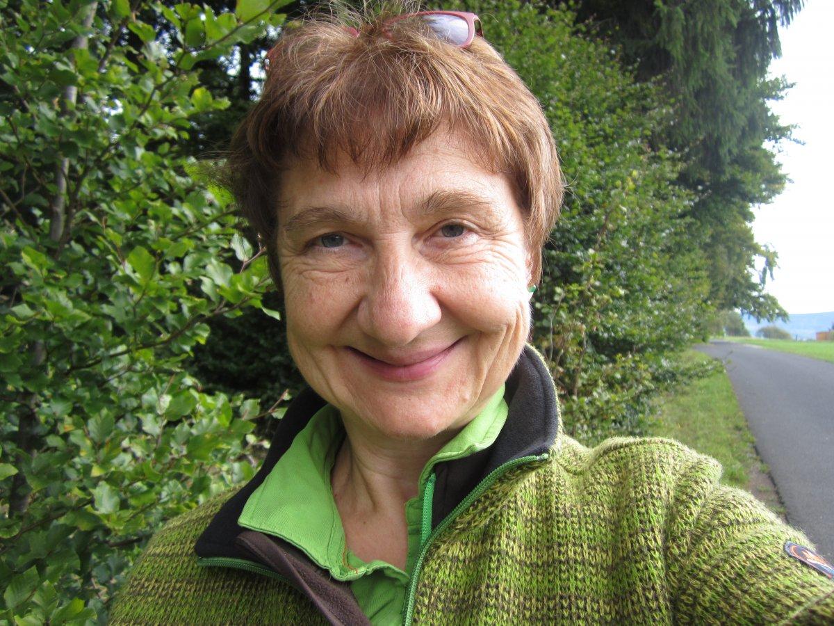 Das Foto zeigt Eva-Maria Hegmann aus Fulda. Im Hintergrund sind Bäume und ein Grünstreifen zu sehen. Sie hat kurze braune Haare und trägt ein grünes T-Shirt und eine grüne Jacke.