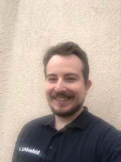 Das Foto zeigt Ray Schönefeld aus Brandenburg an der Havel vor einer hellen Wand. Er hat braune kurze Haare und einen Vollbart.