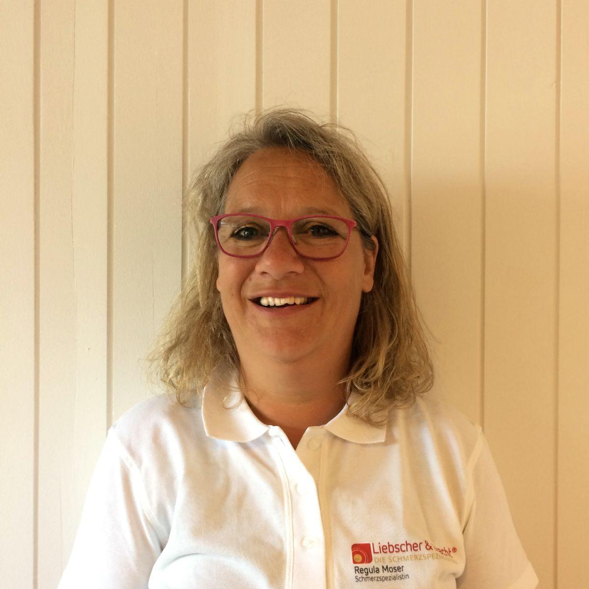Das Foto zeigt Regula Moser vor einer weißen Holzwand. Sie hat hellgraue Haare die sich leicht wellen. Auf dem Foto trägt sie eine rote eckige Brille und ein weißes Liebscher & Bracht Polo T-Shirt.