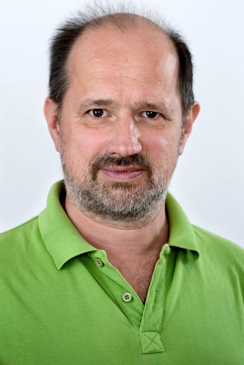Das Foto zeigt Heilpraktiker Ulrich Reiske, vor einem hellen Hintergrund. Er trägt ein grünes Polo T-Shirt und hat eine Halbglatze mit schwarzen Haaren sowie einen schwarz grauen Bart.