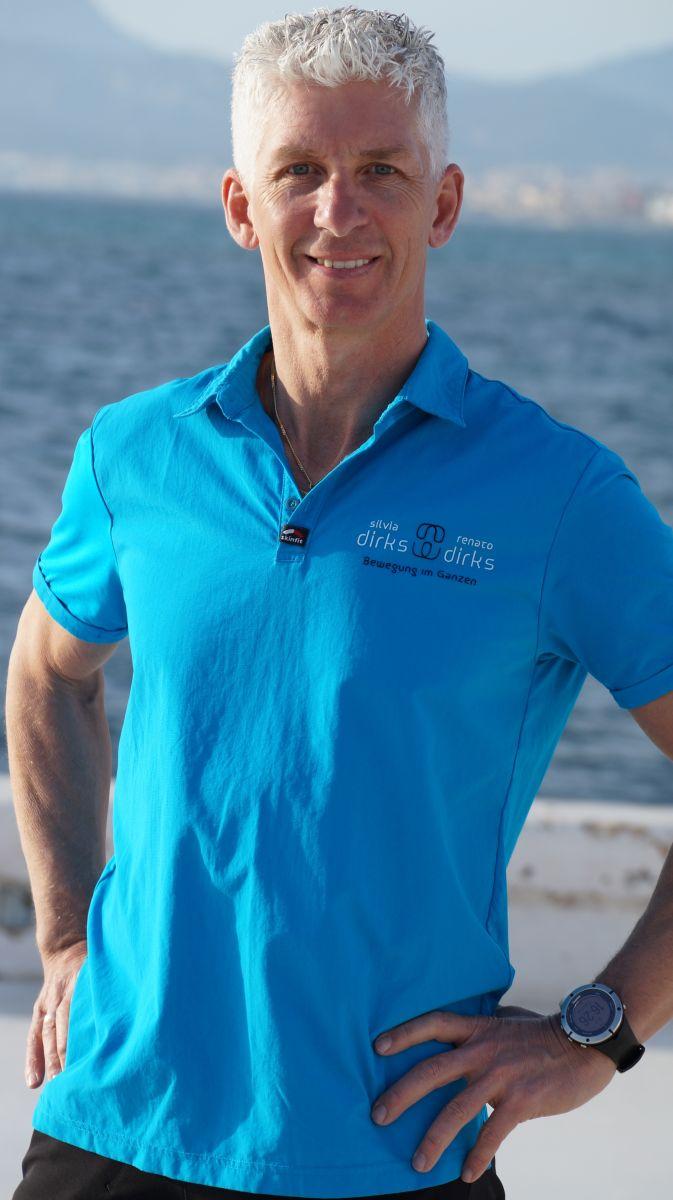 Der Physiotherapeut Renato Dirks steht vor einem Hintergrund mit Wasser. Er hat kurze graue Haare und trägt ein hellblaues Polo T-Shirt. Seine Arme hat er in der Hüfte eingestützt.