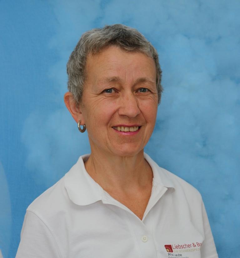 Vor blauen Hintergrund steht Rita Laube aus Winterthur in einem weißen Liebscher & Bracht Polo T-Shirt. Sie hat kurze graue Haare.