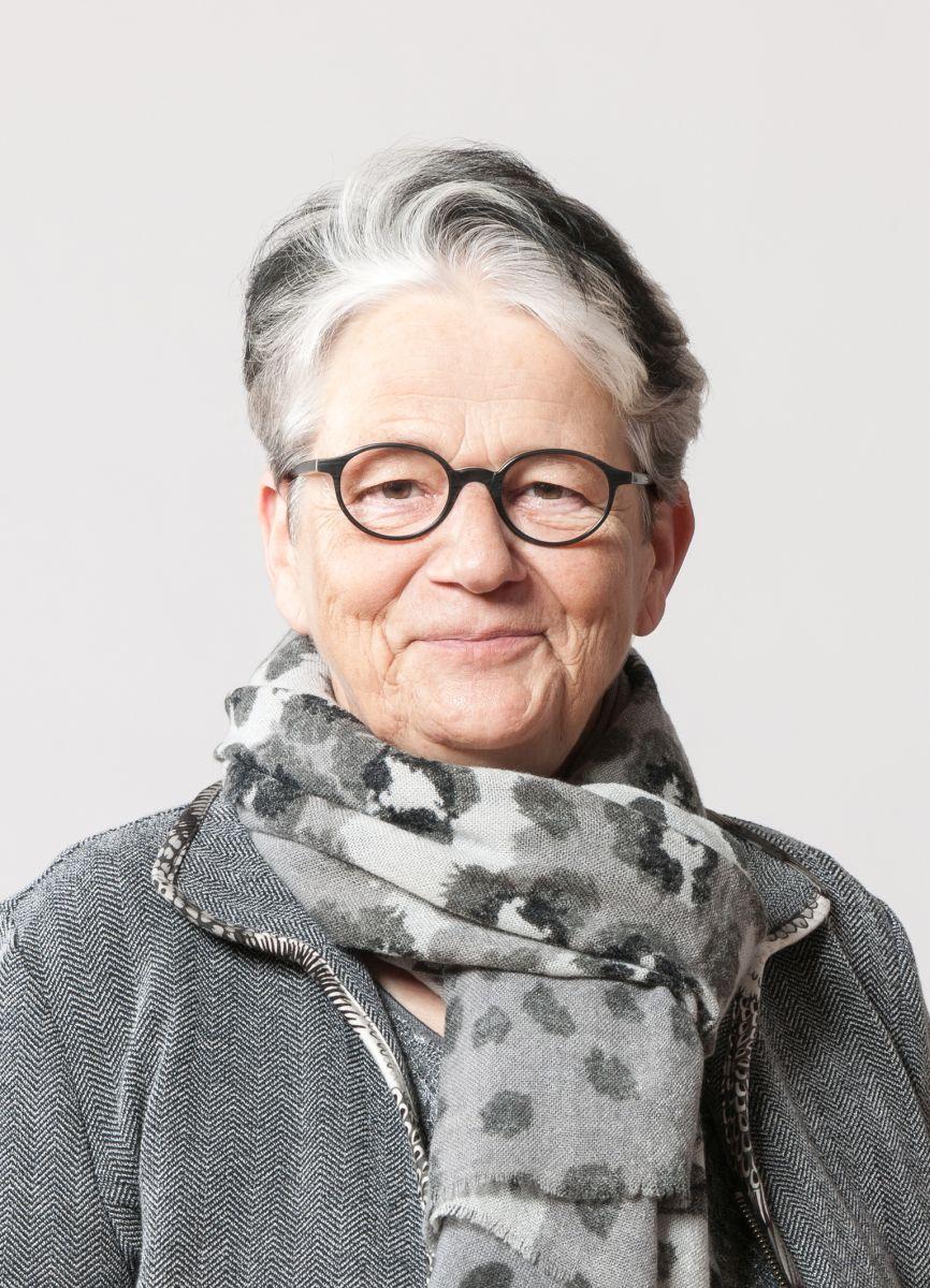 Das Portraitfoto zeigt Rita Schulthess. Sie hat kurze schwarz graue Haare und trägt eine schwarze runde Brille. Dazu trägt sie eine graue Strickjacke und einen dicken grauen gepunkteten Schal. Sie lächelt in direkt in die Kamera.