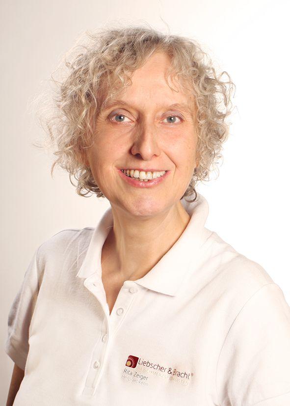Das Foto zeigt Rita Zeiger vor einem weißen Hintergrund. Sie hat helle kinnlange Locken und trägt ein weißes Liebscher & Bracht Polo T-Shirt.