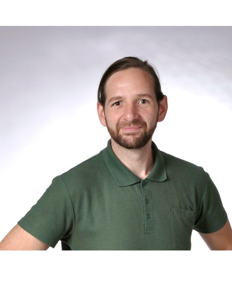 Das Foto zeigt Roland Fuchs aus 63773 Goldbach vor einem hellen, nach außen hin, dunkler werdenden Hintergrund. Er hat kurze braune Haare und einen Vollbart. Auf dem Foto trägt er ein dunkelgrünes Polo T-Shirt.