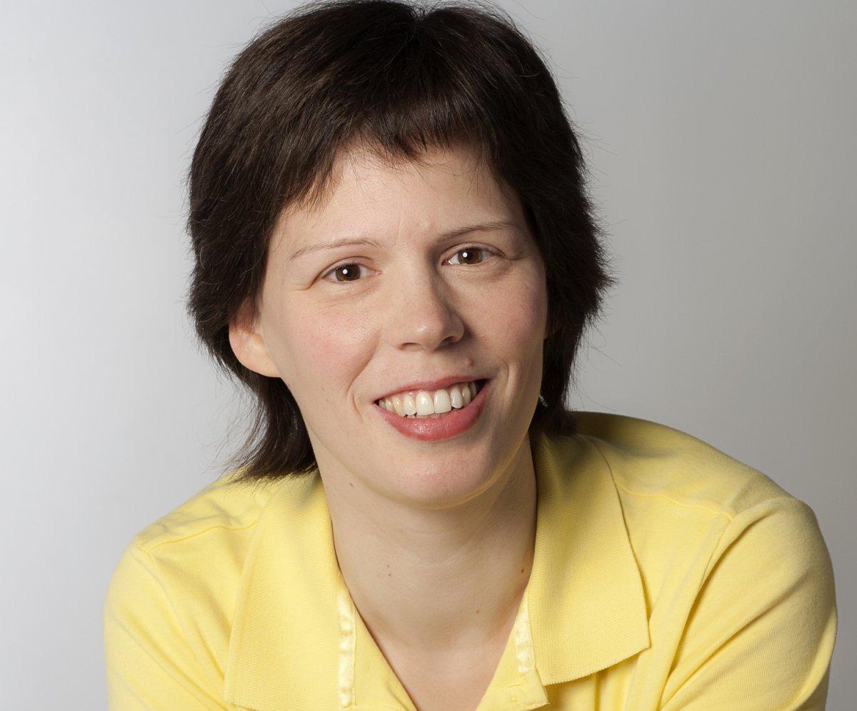 Runa Tost aus Nuthetal in der Nähe von Berlin sieht man vor einem hellgrauen Hintergrund. Sie lächeld, hat mittellange braune Haare und trägt eine gelbe Bluse.