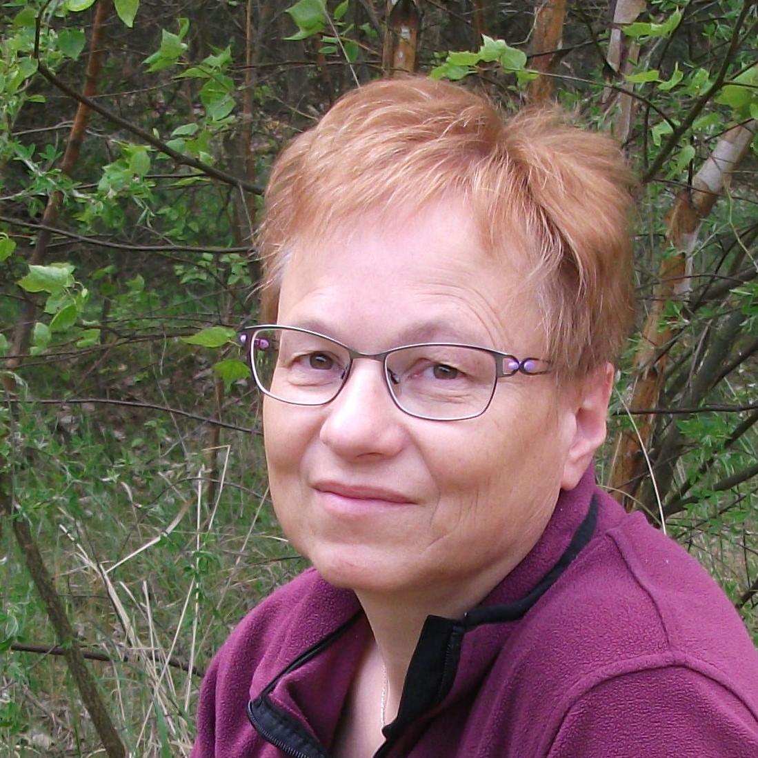 Auf dem Foto steht Sabine Görmar aus 17255 Wesenberg vor einem Hintergrund, der Natur zeigt. Sie hat kurze hellrote Haare und trägt eine lila graue Brille. Außerdem trägt sie eine lila farbene Strickjacke.