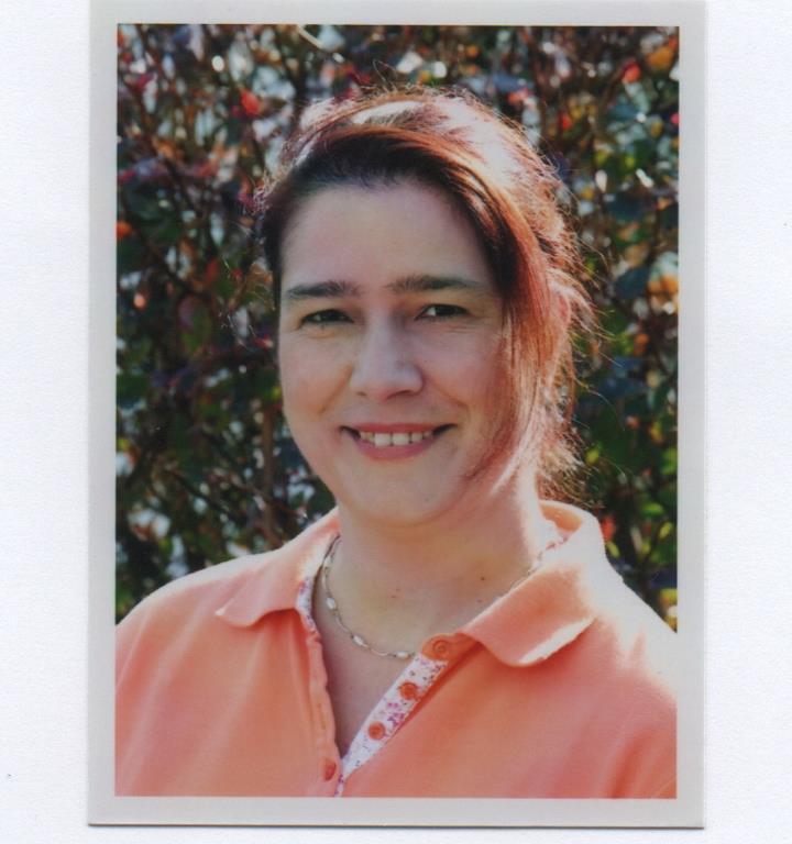 Das Foto zeigt Sandra Kaufmann aus Engelsbrand vor einem rot-grünen Naturhintergrund. Sie hat ihre roten Haare als Zopf gebunden, wobei eine Strähne heraushängt. Auf dem Foto trägt sie ein orangenes Polo T-Shirt und eine silberne Kette.