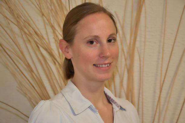 Das Foto zeigt Sara Büchel vor einem hellen Hintergrund mit braunen Strichen. Sie hat ihre braunen Haare als Zopf und steht schräg zur Kamera, in die sie lächelt. Auf dem Foto trägt Sie eine hellblaue Bluse.