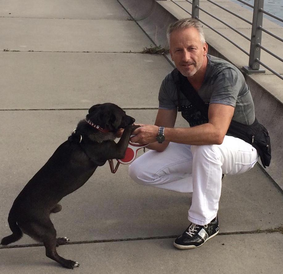 Das Foto zeigt den Gesundheitstrainer Schellenberger knieend neben einem schwarzen Hund, der ihm die Pfote reicht. Schellenberger schaut in die Kamera und hat kurzes graues Haar und trägt ein graues T-Shirt sowie eine weiße Hose.