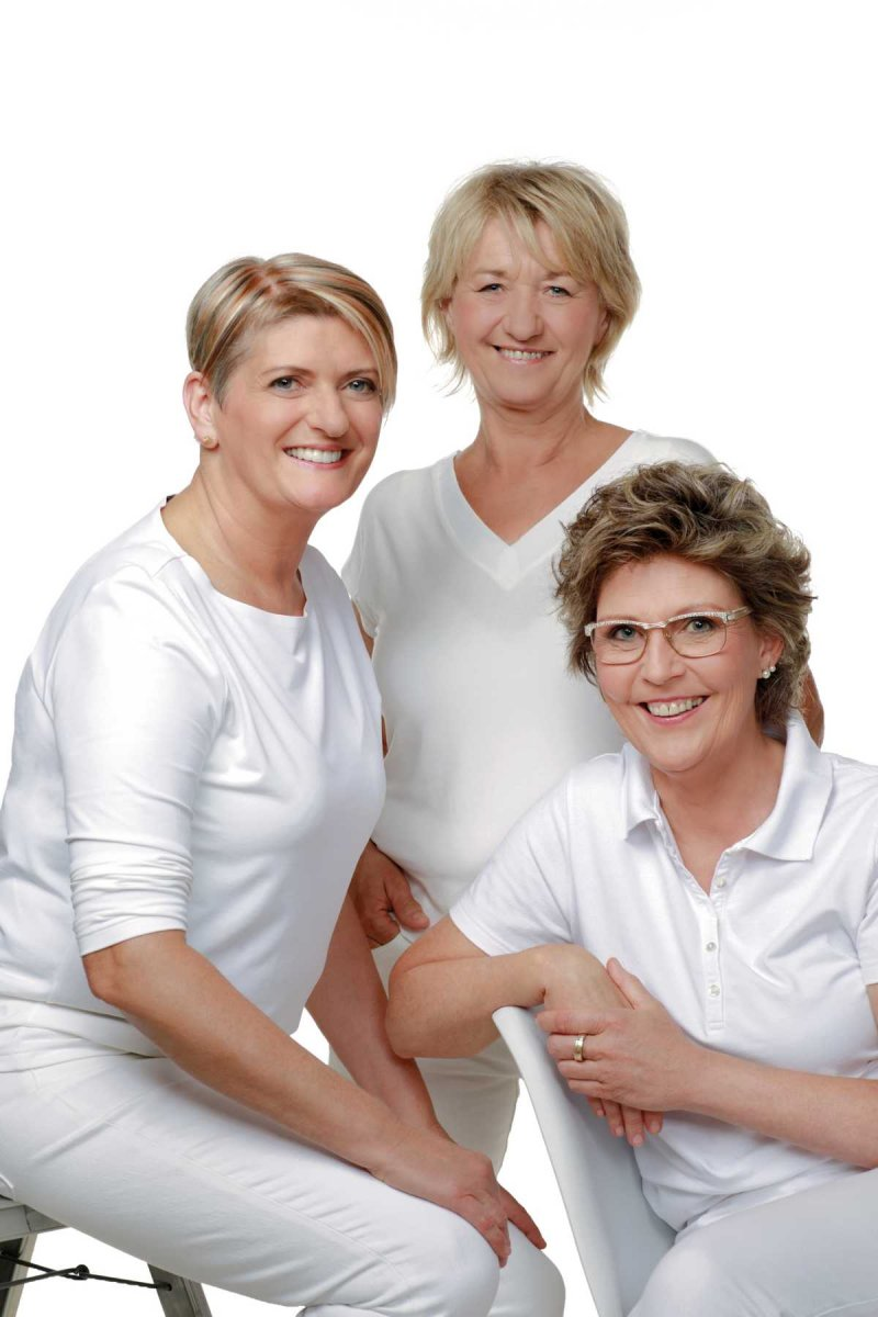 Das Foto zeigt die drei Therapeutinnen Dagmar Wachter, Kristin Keller-Ebert und Gabriele Heckelmann. Sie stehen zusammen auf dem Foto leicht versetzt. Sie tragen alle weiße Kleidung und lächeln in die Kamera.