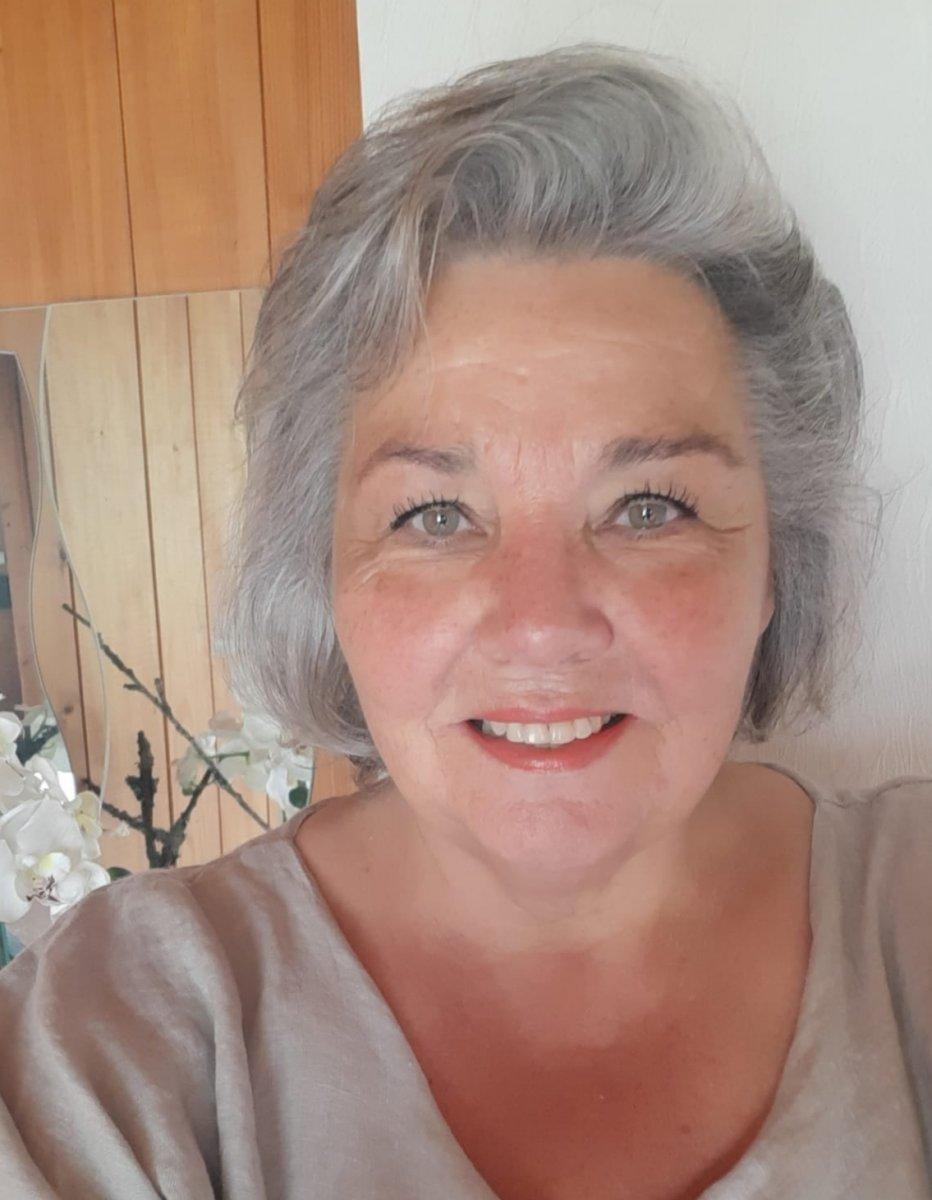 Das Foto zeigt Rosmarie Hossmann. Sie hat kinnlange graue Haare und lächelt in die Kamera. Auf dem Bild trägt sie einen grauen Pullover.