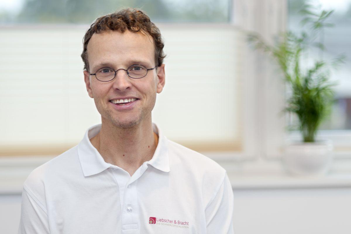 Der Ergotherapeut aus Hanstedt in der Nordheide sitzt vor einem lichtdurchfluteten Fenster. Martin Brandt trägt ein weißes Liebscher & Bracht Polo T-Shirt, hat braune kurze lockige Haare und eine schwarze runde Brille.