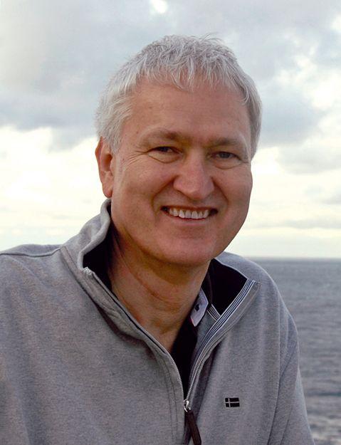 Auf dem Foto ist Siegbert Reichmann aus Recklinghausen zu sehen. Der Hintergrund besteht aus Meer und hellem Himmel. Er trägt eine hellgraue Strickjacke und hat kurzes graues Haar.