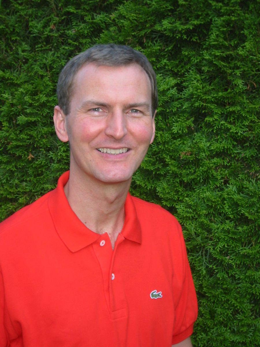 Das Foto zeigt den Heilpraktiker Siegfried Mendler vor einem grünen Busch. Er lacht in die Kamera und hat kurzes braun graues Haar. Auf dem Foto trägt er ein rotes Polo T-Shirt.