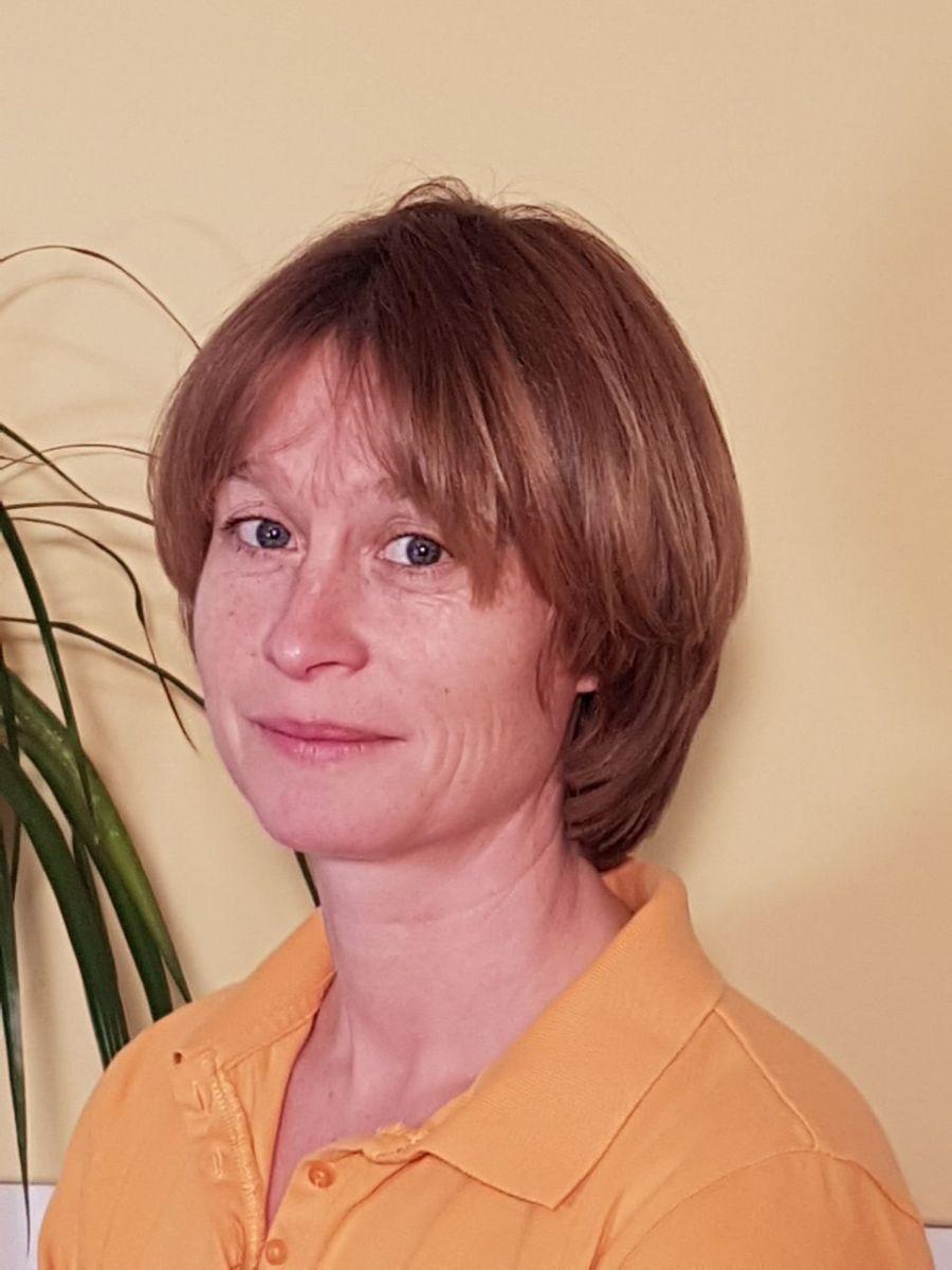 Das Foto zeigt Simone Böck aus 76571 Gaggenau. Sie steht vor einem hellgelben Hintergrund an der am Rand eine grüne Pflanze zu sehen ist. Sie hat braune Haare und trägt ein orangenes Polo T-Shirt.
