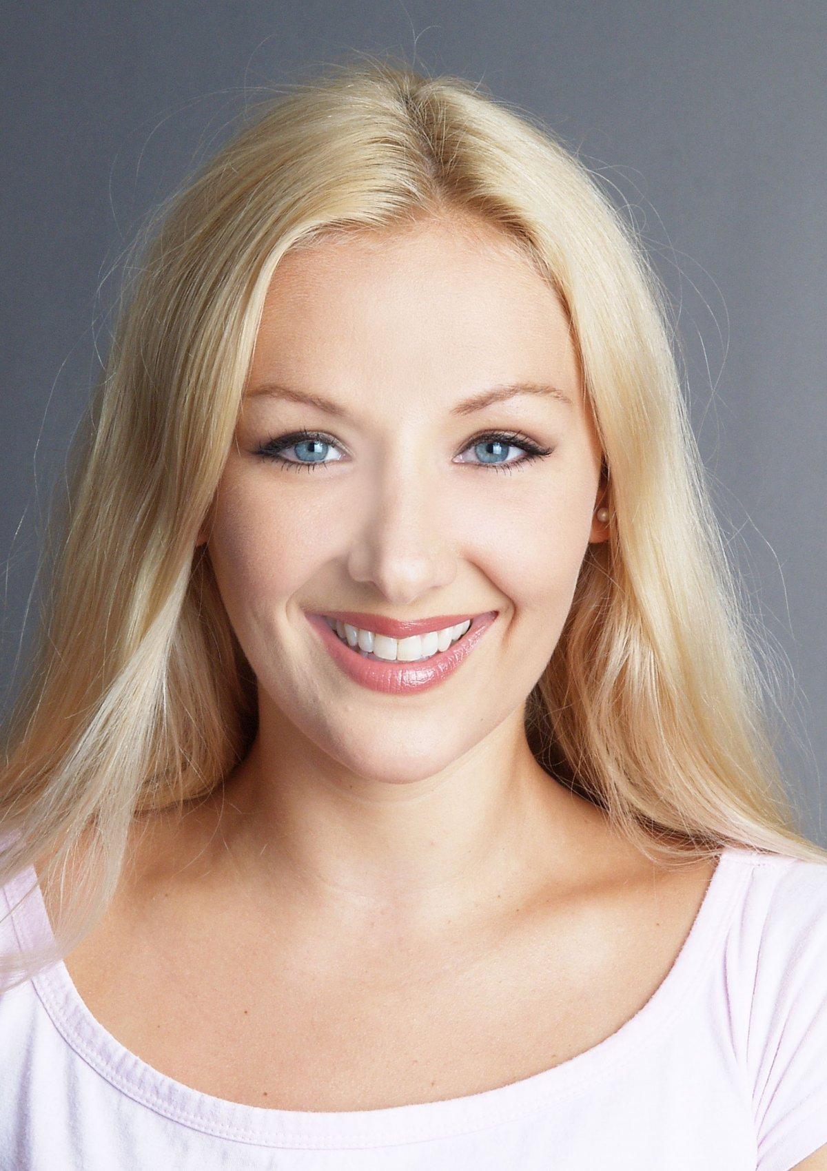 Auf dem Foto ist die hübsche Simone Konstanzer aus 79353 Bahlingen vor einem grauen Hintergrund zu sehen. Sie lacht in die Kamera und hat lange blonde Haare, blaue Augen und trägt ein weißes T-Shirt.
