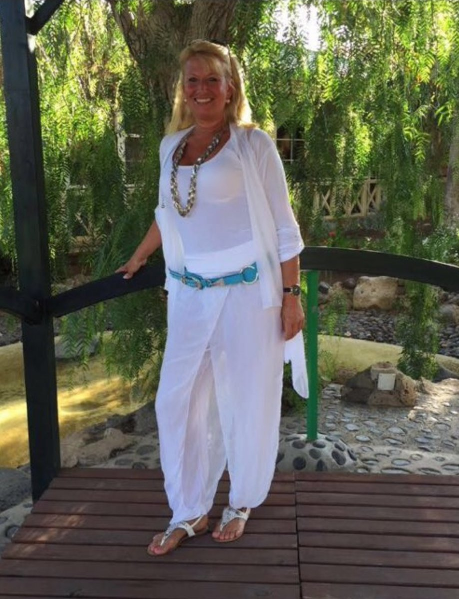 Auf dem Foto steht die Schmerzspezialistin Simone Neumann aus 65343 Eltville am Rhein auf einer Brücke vor einer Trauerweide. Sie trägt ein weißes T-Shirt und Strickjacke und einen weißen Rock. Dazu eine große lange silberne Kette und einen türkisfarbenen