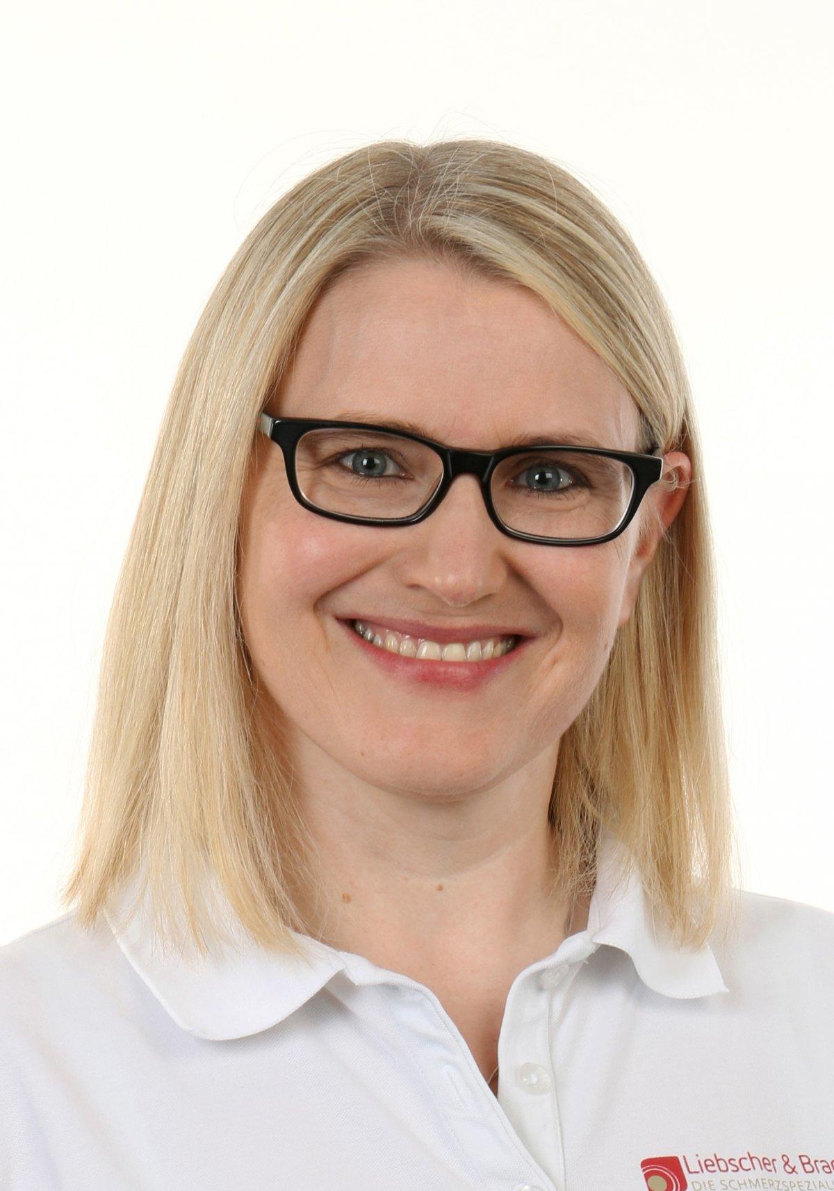 Das Foto zeigt die Physiotherapeutin Sonja Horstmann aus 33332 Gütersloh. Sie hat mittellange blonde Haare und trägt eine schwarze eckige Brille. Dazu trägt sie ein weißes Liebscher & Bracht Polo T-Shirt.